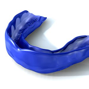 Blue mouthguard for sports resting against white background