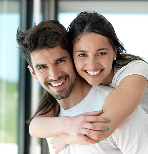 Man and woman with healthy smiles thanks to preventive dentistry