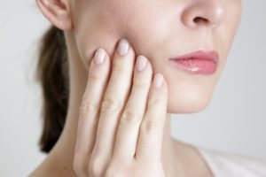 Woman touching jaw, concerned about loose dental implant